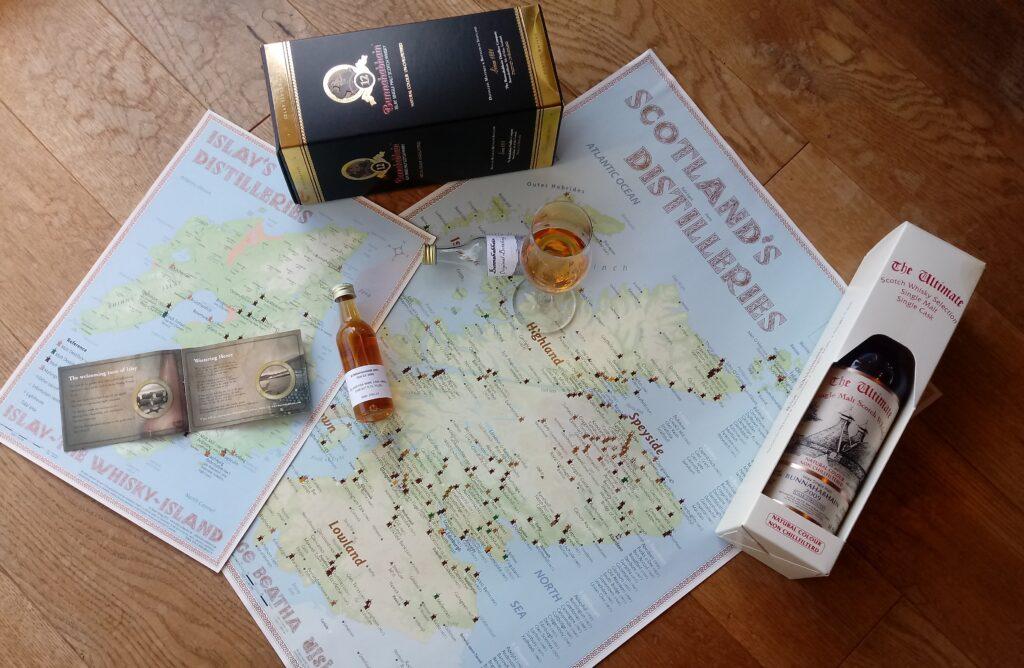 Bild von Whiskysamples, Flaschenkartons, Flaschen sowie zwei Karten von Schottland mit Markierungen für Destillerien